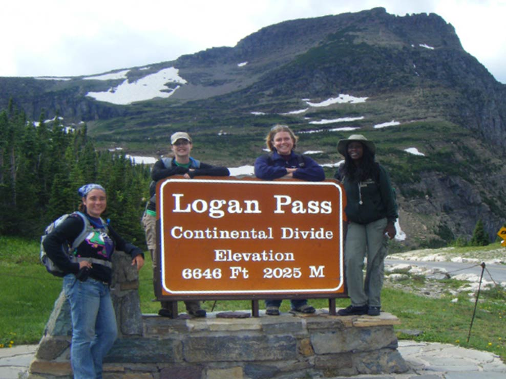 group photo with the logan pass road sign