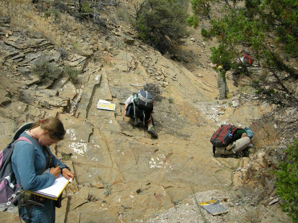 students writing in journals on a rocky slope